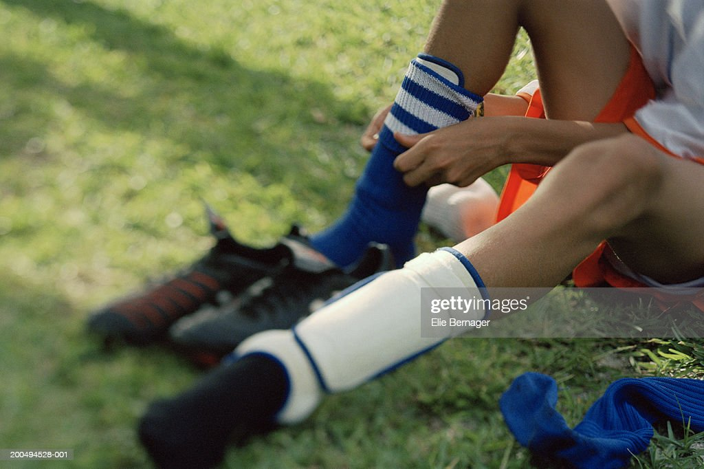 Boy (10-12) putting on socks and shin guards at side of football pitch : Stock Photo