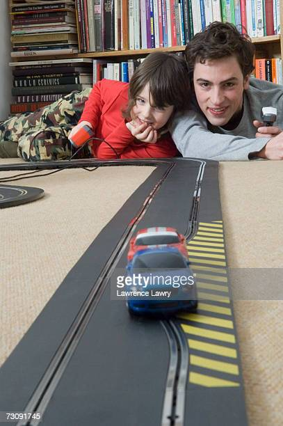Boy (5-7) racing cars with man in living room