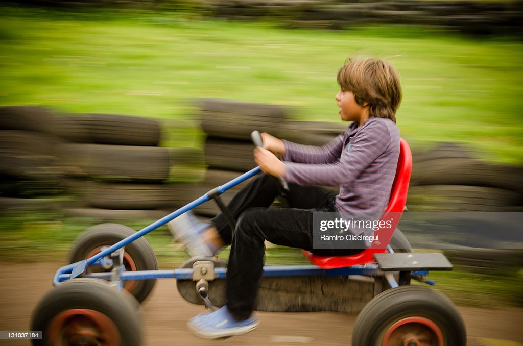 Boy racing on old carting in speed. : Stock Photo