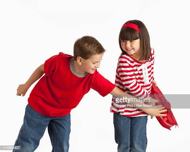 A Boy Reaching For A Heart Shaped Box That A Girl Is Holding Away From Him