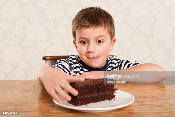 Boy reaching for chocolate cake