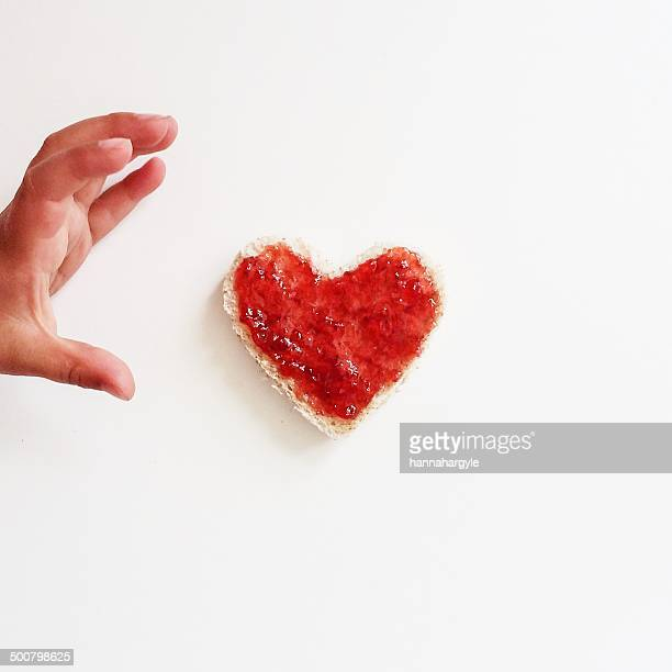 Child's hand with bread and jam heart