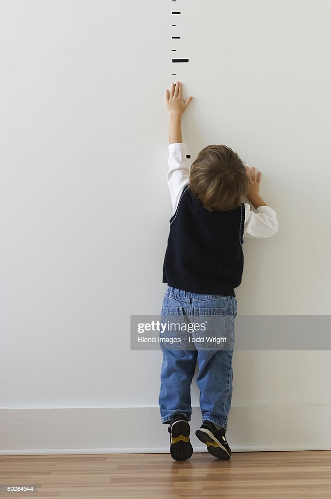 Boy reaching for height markers on wall : Stock Photo