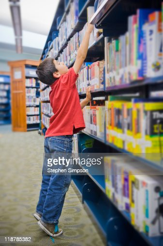 boy reaching high on library shelf : Stock Photo