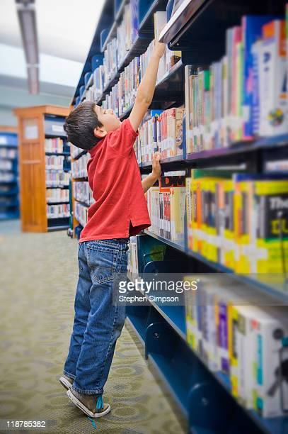 boy reaching high on library shelf