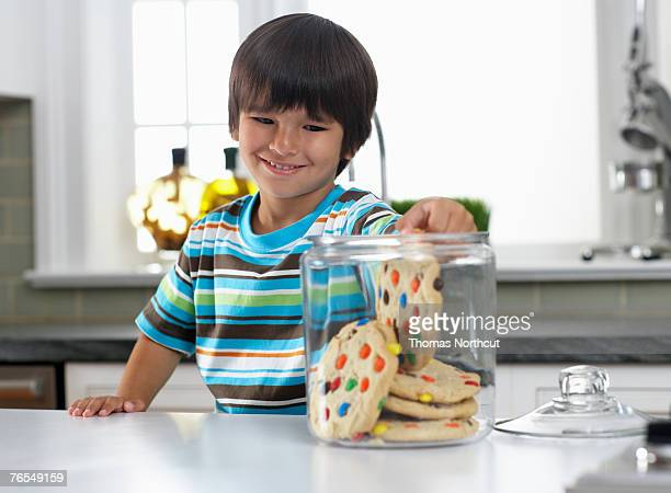 Boy (3-5) reaching into cookie jar on kitchen counter