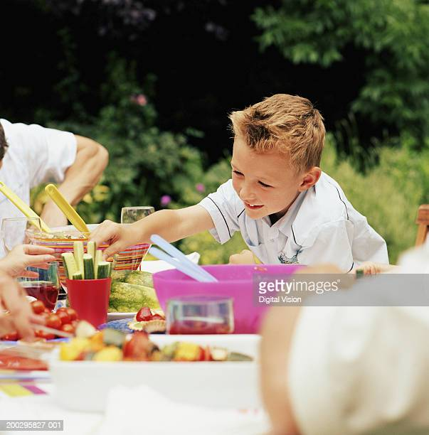 Boy (5-7) reaching over dinner table in garden, picking cucumber stick