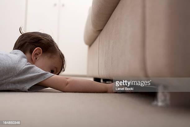 A boy reaching under a sofa to retrieve something