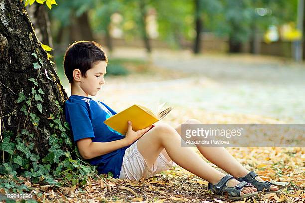 Boy reading a book by a tree in the park