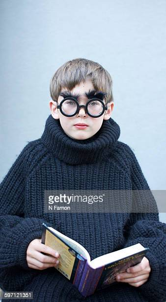 Boy reading a book in funny glasses.