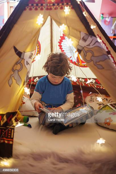 Boy reading a book in the tepee
