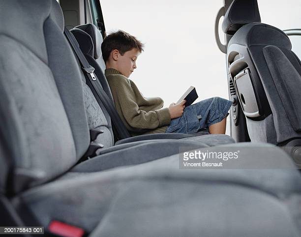 Boy (7-9) reading book in back of car, profile