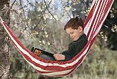 Boy (4-7) reading book in hammock, side view