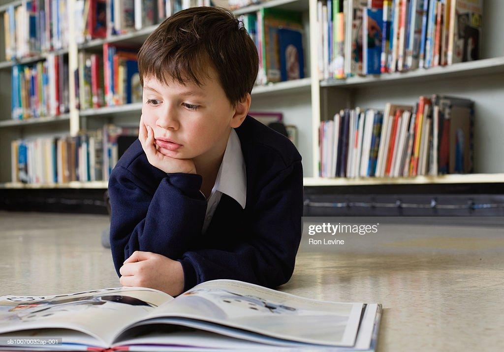 Boy (6-7) reading book in school library