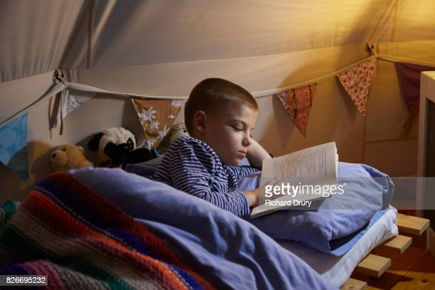 Boy reading book in tent at night