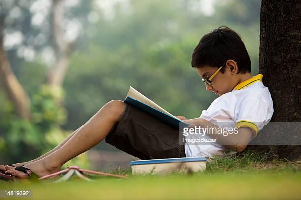 Menino (6- 7) Ler livros no Parque debaixo da árvore