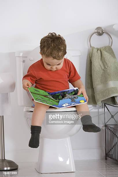 Boy reading children's book while sitting on toilet