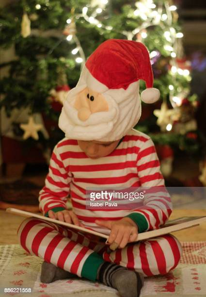 Boy reading Christmas book in front of Christmas tree