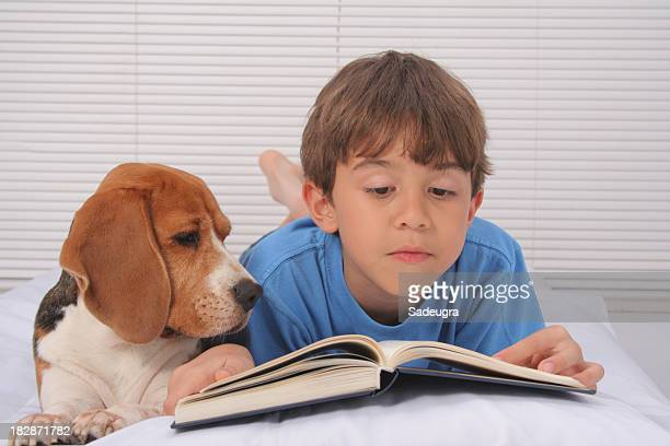 A boy reading in bed with his puppy