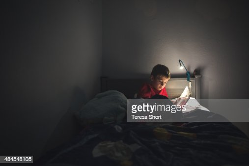 boy reading in bed with reading lamp stock photo getty images. Black Bedroom Furniture Sets. Home Design Ideas