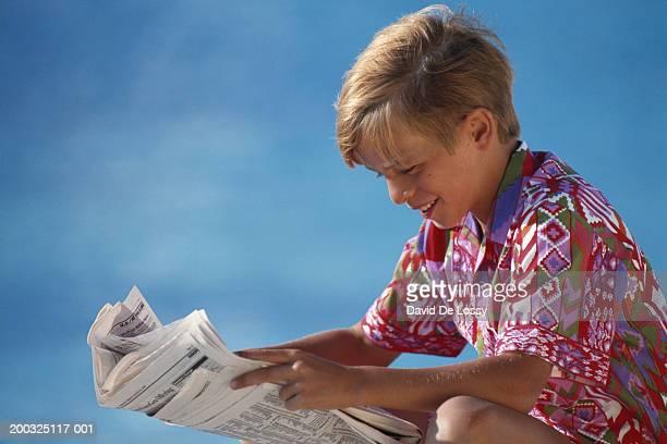 Boy (10-13) reading newspaper, smiling