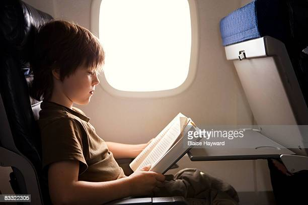 Boy reading on plane