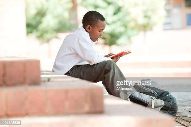 Boy reading on steps outside school, Johannesburg, Gauteng Province, South Africa