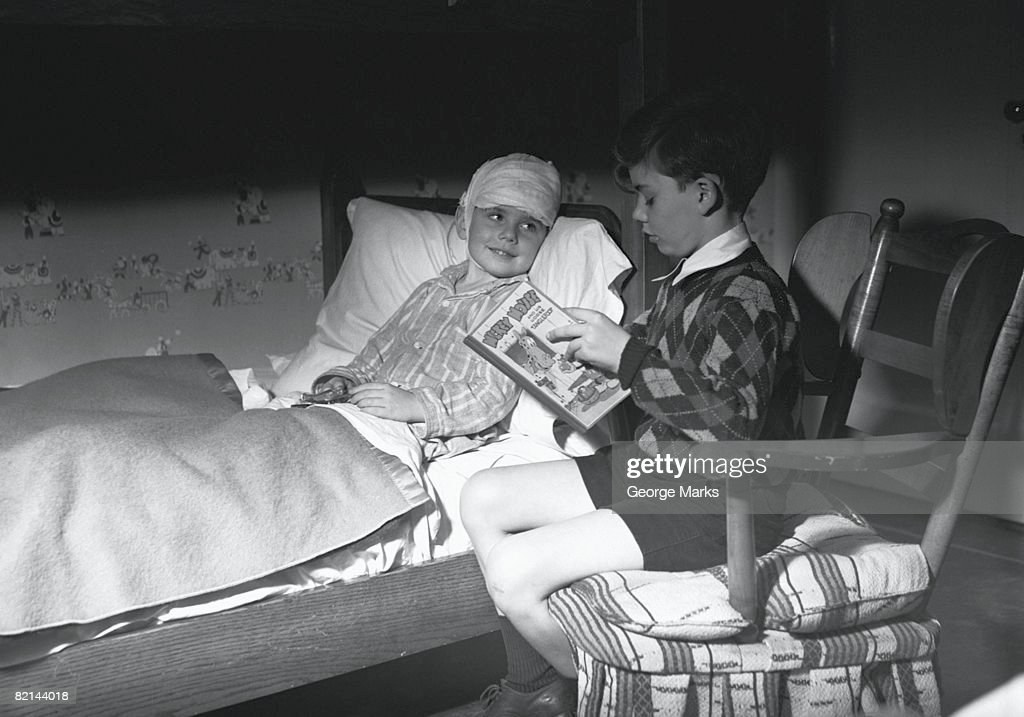 Boy (10-11) reading to friend lying in bed, (B&W) : Stock Photo