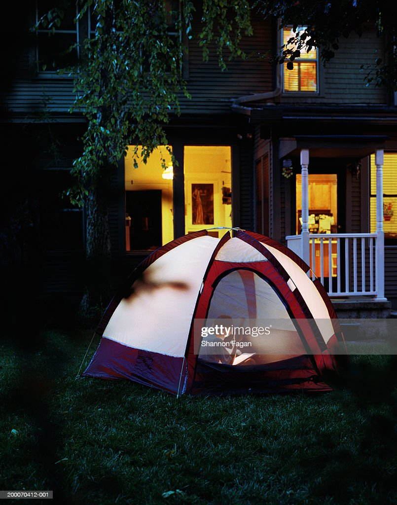 Boy (10-12) reading with flashlight in tent outside home : Stock Photo