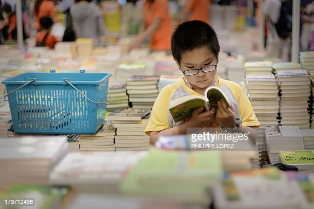 A boy reads a book at the Hong Kong Book Fair on July 17 2013 The fair opened as tens of thousands of book lovers expected to flock to the sevenday...