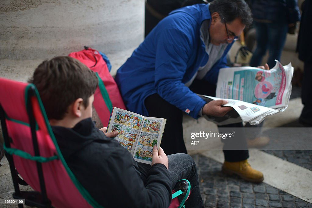 A boy reads a comic book under the colonnade as faithfuls wait for the smoke announcing the result of the conclave on March 13, 2013 at the Vatican. The 115 cardinals held a first inconclusive vote in the Sistine Chapel yesterday as they began the process of finding a successor to Benedict XVI, who brought a troubled eight-year papacy to an abrupt end by resigning last month.
