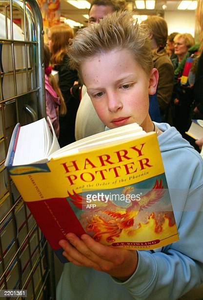 A boy reads a copy of 'Harry Potter and the Order of the Phoenix' while queueing to buy the book in Helsinki 22 June 2003 at a bookstore which opened...