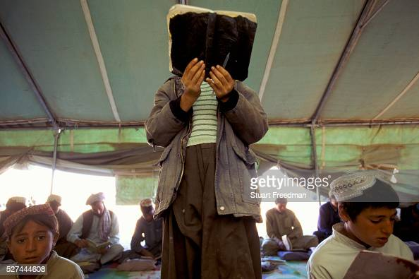 Boy reads his Koran Boys in an Internally Displaced Persons Camp called Zahri Dosht