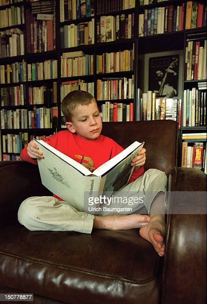 A boy reads in front of a wall of books