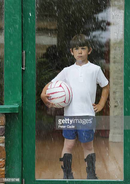 Boy ready to play football looking out at rain