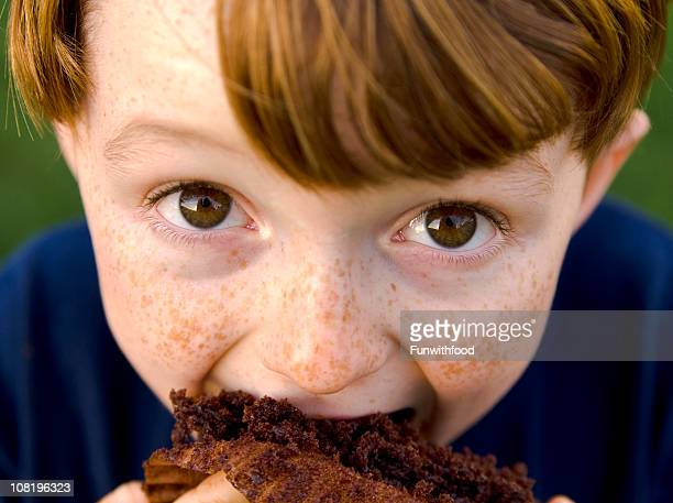 Boy Redhead & Funny Freckle Face Child Eating Unhealthy Chocolate Cupcake