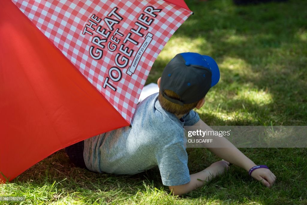 A boy relaxes under an umbrella in hot weather at a 'Great Get Together' community service and picnic in memory of murdered Member of Parliament Jo Cox, marking the first anniversary since her killing, in the grounds of All Saints Church in Batley, northern England on June 18, 2017. The Great Get Together weekend is Inspired by murdered Labour MP Jo Cox's belief that we have more in common than which divides us, a line from her first speech to Parliament, and is a community initiative designed to unite people and communities on the streets and parks of their neighbourhoods. The 41 year-old Labour Party MP, Jo Cox, was assassinated by a pro-Nazi sympathiser in a terror attack in her constituency in northern England on June 16, 2016. /