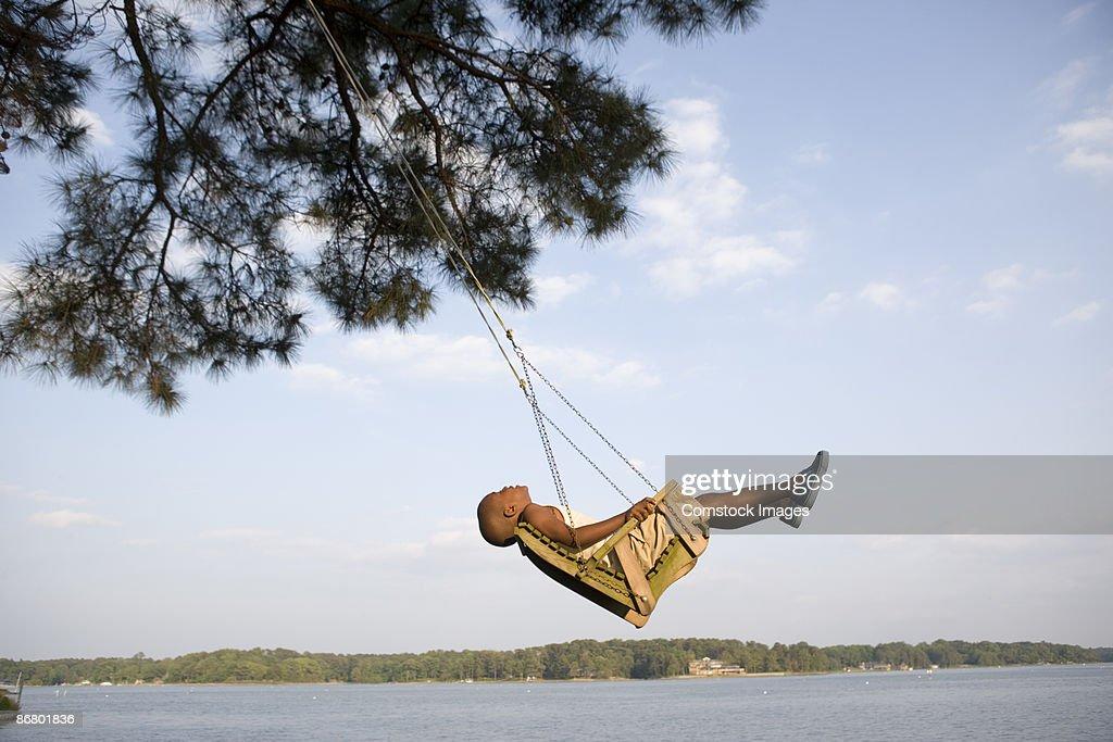 Boy relaxing in swing by lake : Stock Photo