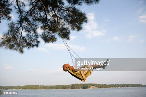 Boy relaxing in swing by lake : Stock Photo