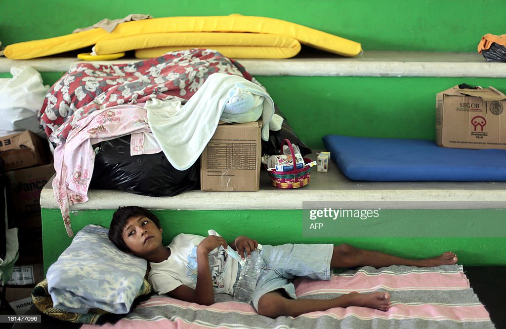 A boy remains at a shelter in Acapulco, Guerrero state, Mexico on September 21, 2013. Mexico looked Saturday to the Herculean task of rebuilding after a rare double onslaught of storms, with nearly 170 people feared dead in the path of destruction. AFP PHOTO/ Pedro Pardo