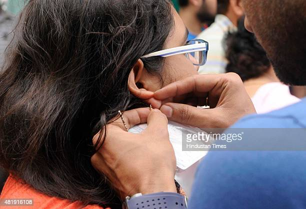 A boy removes gold earrings from her AIPMT aspirant sister as earrings were not allowed due to dress code at the entrance of Examination center at a...