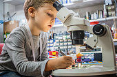Little boy looking through microscope and examining mother board during science lesson. Kid repairing computer part in IT lab.