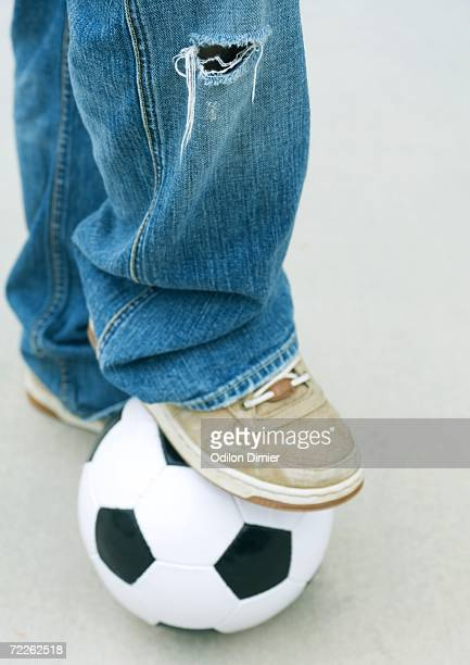 Boy resting foot on soccer ball, close-up