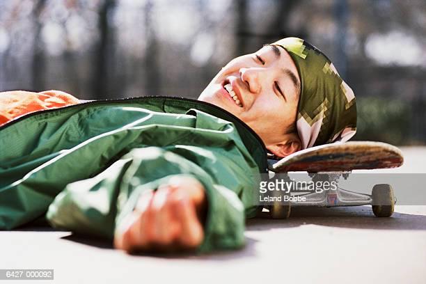 Boy Resting Head on Skateboard