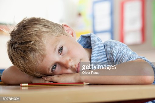 Boy resting on desk in classroom : Stockfoto