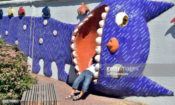 A boy rests in a sculpture in a children's playground in the center of Ukrainian capital of Kiev on June 21 2017 as Europe sizzled in a continentwide...