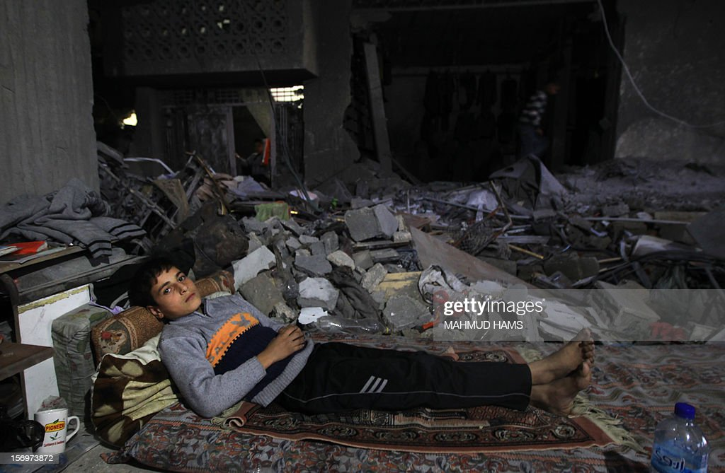 A boy rests on a mattress laid out in the rubble of a destroyed building in Beit Lahia, in the northern Gaza Strip, on November 26, 2012, following a truce last week between Israel and Hamas that ended eight days of conflict in which 166 Palestinians and six Israelis were killed. AFP PHOTO/MAHMUD HAMS