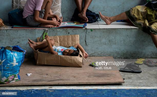 A boy rests on a paper carton inside a covered basketball court turned into an evacuation center for the Marawi City evacuees at Maria Cristina...