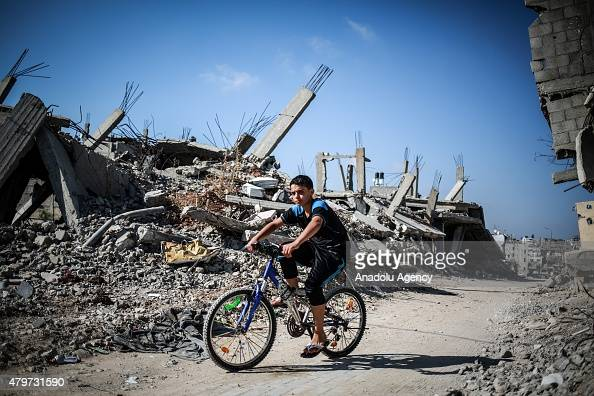 A boy ride a bike near the debris of buildings in the Shuja'iyya neighborhood which was badly damaged in Israel's most recent attacks on the Gaza...