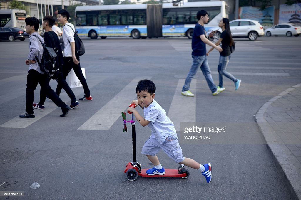 A boy rider a step scooter whlie crossing a street in Beijing on May 30, 2016. / AFP / WANG